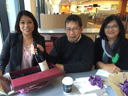 Jun Relunia's retirement tea from Woolworths with his friends Beth Morrell  (left)  and Kate Andres (right )